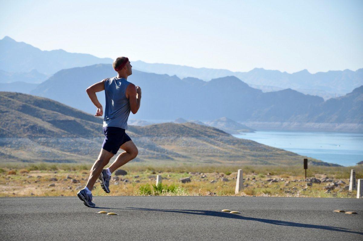 Man hardlopen op asfalt in bergen